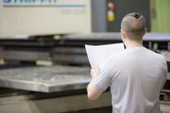 Чертеж взгляда работника человека blueprints в мастерской фабрики Стоковые Фотографии RF