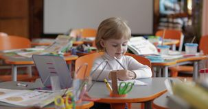 Чертеж девушки на таблице в классе Образование Ребенок сидя на столе акции видеоматериалы