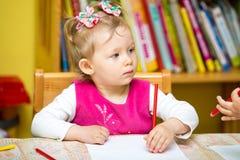 Чертеж девушки ребенка с красочными карандашами в preschool на таблице в детском саде Стоковые Изображения
