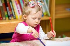 Чертеж девушки ребенка с красочными карандашами в preschool на таблице в детском саде Стоковое Фото