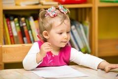 Чертеж девушки ребенка с красочными карандашами в preschool на таблице детсад девушки немногая Стоковые Изображения RF