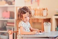 Чертеж девушки ребенка Preschooler с карандашами дома Стоковое фото RF