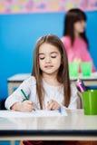 Чертеж девушки с ручкой эскиза в Preschool Стоковое Изображение