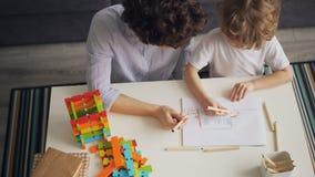 Чертеж маленького ребенка и крася изображение с осторожной матерью на таблице дома акции видеоматериалы