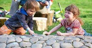 Чертеж мальчика и девушки с тротуаром белит мелом в парке Стоковое фото RF