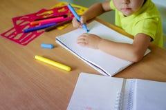 Чертеж мальчика с crayons цвета стоковые фото