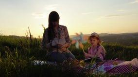 Чертеж матери и дочери на пикнике на холме в лете на заходе солнца видеоматериал