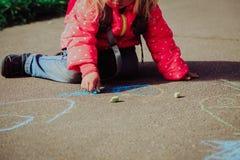 Чертеж маленькой девочки на асфальте после школы стоковое изображение