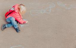 Чертеж маленькой девочки на асфальте после школы стоковое фото