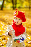 Чертеж ребенка на мольберте в парке осени. Творческое развитие детей стоковые изображения rf