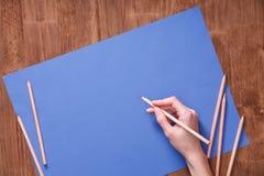 Чертеж руки девушки, пустая голубая бумага и красочные карандаши на деревянном столе Стоковые Изображения RF