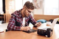 Чертеж человека фрилансера на таблетке на компьтер-книжке сидя на столе Стоковые Фотографии RF