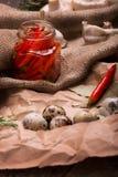 Чеснок, банк горячих красных перцев, яичка триперсток и розмариновое масло на скомканной бумажной и деревенской ткани ингридиенты Стоковые Фото