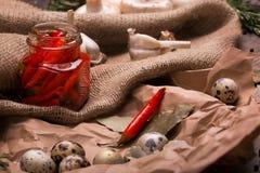 Чеснок, банк горячих красных перцев, яичка триперсток и розмариновое масло на скомканной бумажной и деревенской ткани ингридиенты Стоковое фото RF