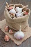 Чеснок в сумке на деревянной предпосылке Стоковые Фото