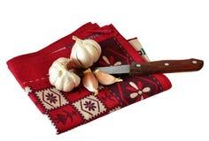 Чеснок и нож на красном полотенце Стоковое Фото