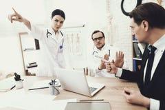 Честные доктор и медсестра отказывают принять взятку от пациента в медицинском офисе стоковое фото rf