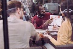 Честолюбивые 3 коллеги наблюдающ диаграммой Стоковые Изображения