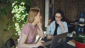 Честолюбивые enterpreneurs начинают стратегию бизнеса сидя в современном офисе и говорить стиля просторной квартиры Одно из их акции видеоматериалы
