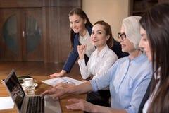 Честолюбивые коллеги используя компьтер-книжку в офисе Стоковая Фотография