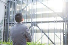 Честолюбивый бизнесмен от задней части - смотреть стеклянное здание Стоковое Фото