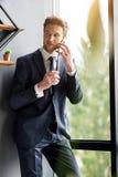 Честолюбивый молодой бизнесмен связывает телефоном Стоковые Изображения RF