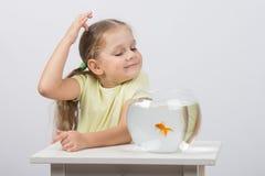 Четырехклассная девушка делает желание пока наслаждающся рыбкой в аквариуме Стоковое Изображение