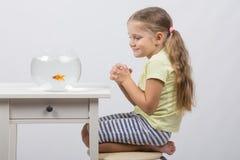 Четырехклассная девушка делает желание сидя перед рыбкой Стоковые Фото