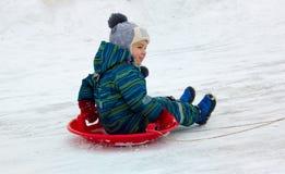 Четырехлетний ребенок, мальчик, ехать скелетон от скольжения снега стоковое фото