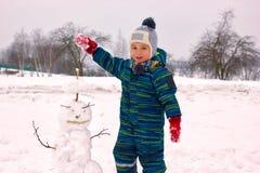 Четырехлетний ребенок, мальчик, усмехаясь ваяет снеговик стоковые фото