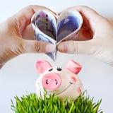 Чехословакские бумажные деньги в форме сердца с руками над piggy Стоковые Изображения RF