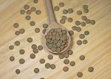 Чечевицы в деревянной ложке на деревянной предпосылке Стоковая Фотография