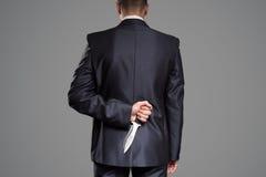 Человека тайника ножа задняя часть позади Концепция убийцы стоковое изображение