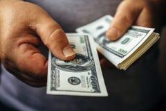 Человек давая 100 банкнот доллара США и держа получает внутри руки наличными Стоковая Фотография RF