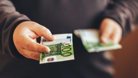 Человек давая наличные деньги денег Мужские руки держа 100 счетов банкноты евро кредит Стоковые Изображения RF