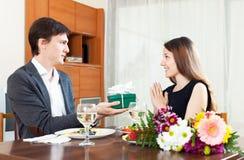 Человек давая подарок к девушке стоковые изображения