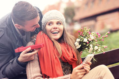 Человек давая подарок сюрприза к женщине в парке стоковая фотография