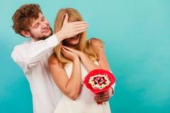 Человек давая пук конфеты женщины покрывая ее глаза Стоковая Фотография