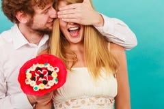 Человек давая пук конфеты женщины покрывая ее глаза Стоковые Фотографии RF