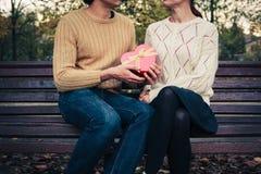 Человек давая сердцу женщины форменную коробку Стоковая Фотография
