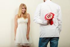 Человек давая цветки пука конфеты женщины Любовь Стоковая Фотография