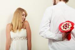 Человек давая цветки пука конфеты женщины Любовь Стоковые Изображения RF