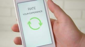 Человек дает оценку 5 звезд используя применение smartphone акции видеоматериалы