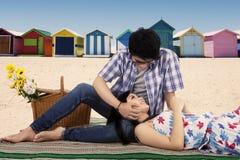 Человек ласкает его подругу на пляже Стоковые Фото