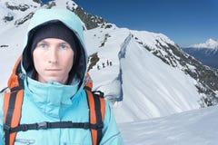 Человек альпиниста стоит в горах зимы, идти Snowboarders гористый для freeride на заднем плане Стоковое Изображение