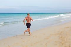 Человек бежать на пляже стоковая фотография