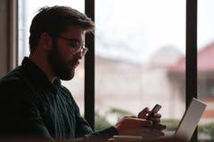 Человек беседуя телефоном и используя портативный компьютер Стоковое Фото