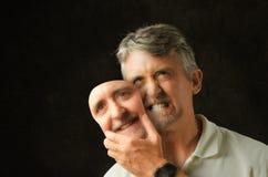 Человек биполярного расстройства сердитый эмоциональный с поддельной маской улыбки стоковая фотография