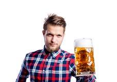 Человек битника в проверенной рубашке держа пиво, съемку студии Стоковая Фотография