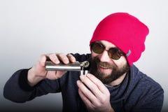 Человек битника моды холодный в солнечных очках и красочных одеждах льет питье от склянки металла Стоковая Фотография